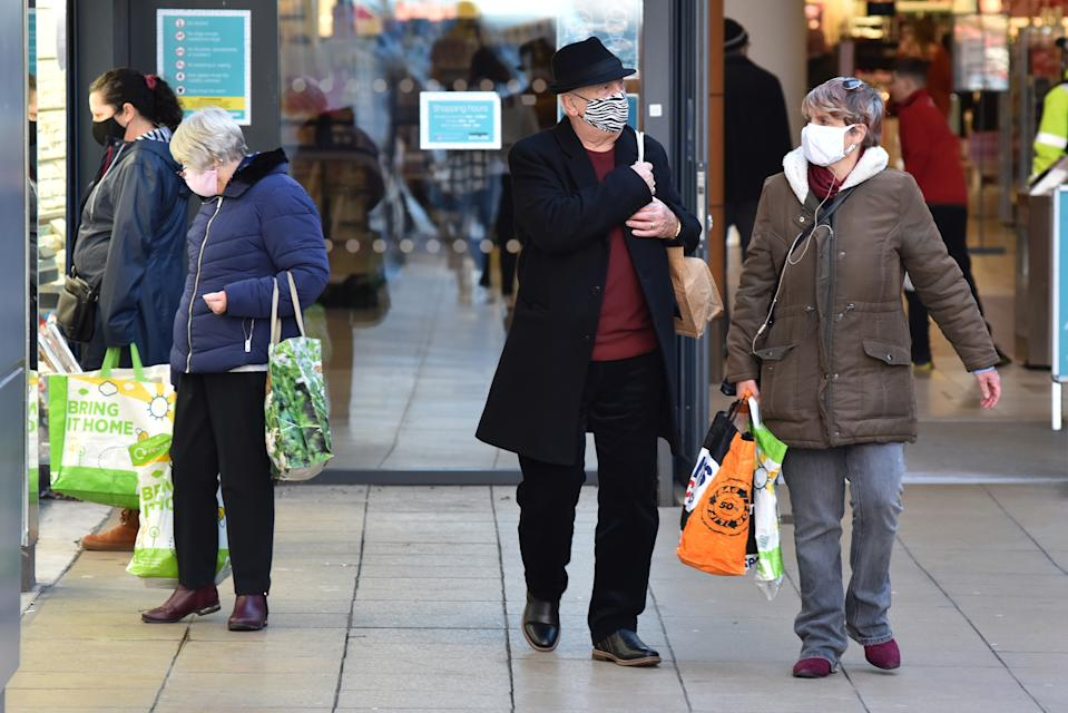 BASILDON, ENGLAND - DECEMBER 17: People wear face masks while out shopping on December 17, 2020 in Basildon, England. As Coronavirus cases continue to rise across the country, Basildon in Essex has the third-highest infection rate with 696.1 cases per 100,000 behind Swale and Medway, both in Kent.  (Photo by John Keeble/Getty Images)