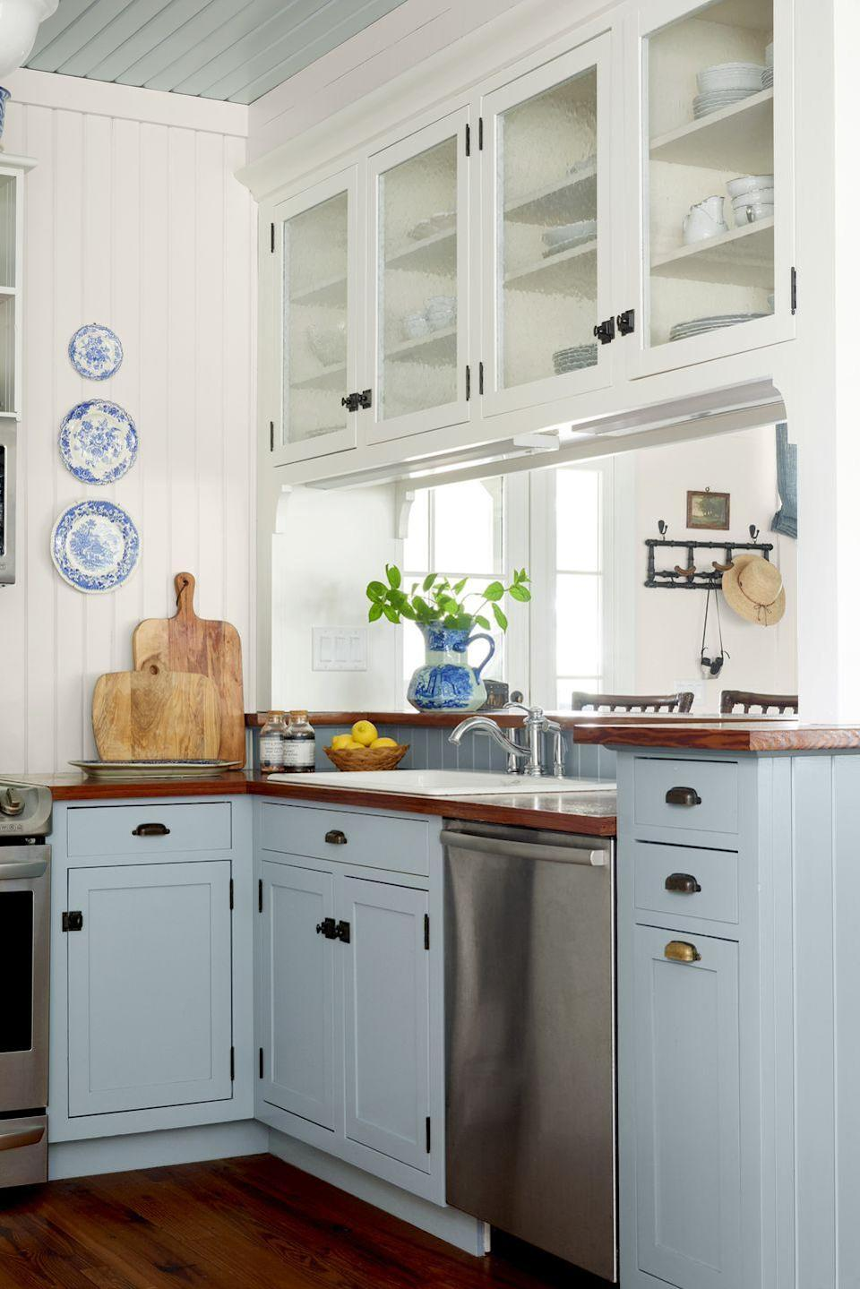 """<p>Air out an itty-bitty kitchen with two-tone cabinets. Designer Heather Chadduck Hillegas outfitted this small space with <a href=""""https://www.sherwin-williams.com/homeowners/color/find-and-explore-colors/paint-colors-by-family/SW0050-classic-light-buff"""" rel=""""nofollow noopener"""" target=""""_blank"""" data-ylk=""""slk:Classic Light Buff by Sherwin-Williams"""" class=""""link rapid-noclick-resp"""">Classic Light Buff by Sherwin-Williams</a> on the upper cabinets and <a href=""""https://www.sherwin-williams.com/homeowners/color/find-and-explore-colors/paint-colors-by-family/SW9139"""" rel=""""nofollow noopener"""" target=""""_blank"""" data-ylk=""""slk:Debonair by Sherwin-Williams"""" class=""""link rapid-noclick-resp"""">Debonair by Sherwin-Williams</a> on the lower cabinets.</p>"""