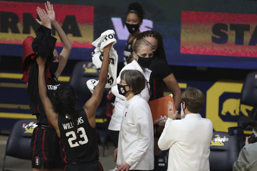 Stanford head coach Tara VanDerveer, bottom center, walks off the court after an NCAA college basketball game against California, Sunday, Dec. 13, 2020, in Berkeley, Calif. With the victory, VanDerveer tied Pat Summitt's record for most career wins by a women's basketball coach at 1,098 wins. (AP Photo/Jed Jacobsohn)