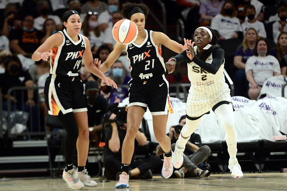 Kahleah Copper passes the ball to a player out of frame with Mercury players in the background.