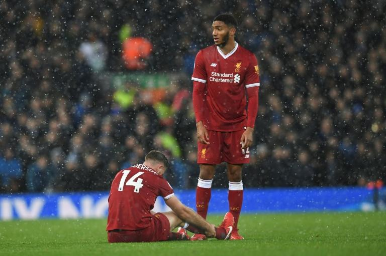 Liverpool's Joe Gomez (R) stands next to injured teammate Jordan Henderson during their English Premier League match against Everton, at Anfield in Liverpool, on December 10, 2017