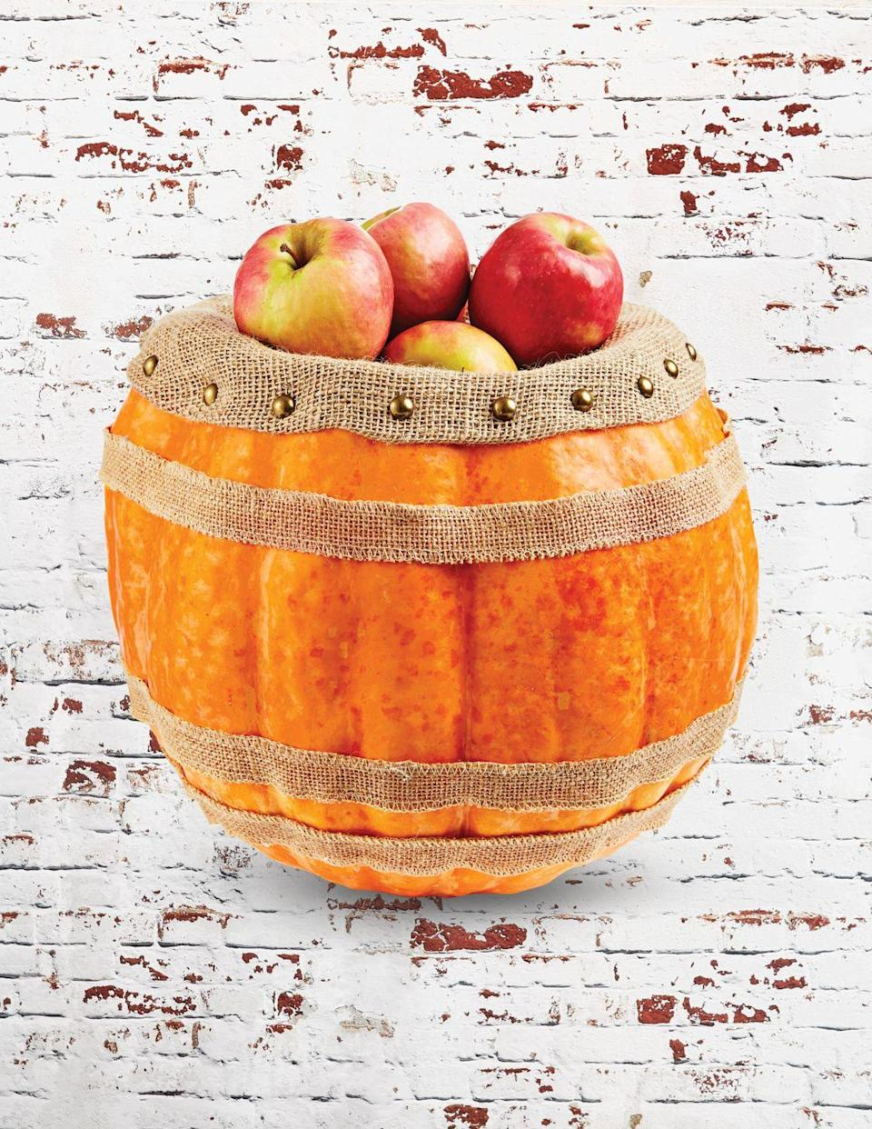 """<p>Talk about adorable fall porch decor. This """"barrel"""" is the perfect way to show off your <a href=""""https://www.countryliving.com/life/travel/g2623/apple-picking/"""" rel=""""nofollow noopener"""" target=""""_blank"""" data-ylk=""""slk:apple-picking"""" class=""""link rapid-noclick-resp"""">apple-picking</a> treasures!</p><p><strong>Make the barrel: </strong>Cut off the top quarter of an extra-large pumpkin; scoop out pulp and seeds. Hot-glue three strips of burlap ribbon around outside of pumpkin. Stuff pumpkin three-fourths full with Poly-Fil. Insert burlap fabric into the opening and fold over outside of pumpkin; hold in place with upholstery tacks. Fill with apples or desired items. </p>"""