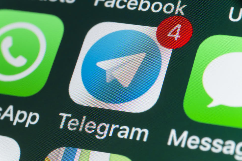 The Telegram app on a phone screen alongside other apps.