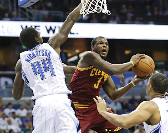 Cleveland Cavaliers' Dion Waiters (3) tries to shoot between Orlando Magic's Andrew Nicholson (44) and Tobias Harris, right, during the first half of an NBA preseason basketball game in Orlando, Fla., Friday, Oct. 11, 2013. (AP Photo/John Raoux)