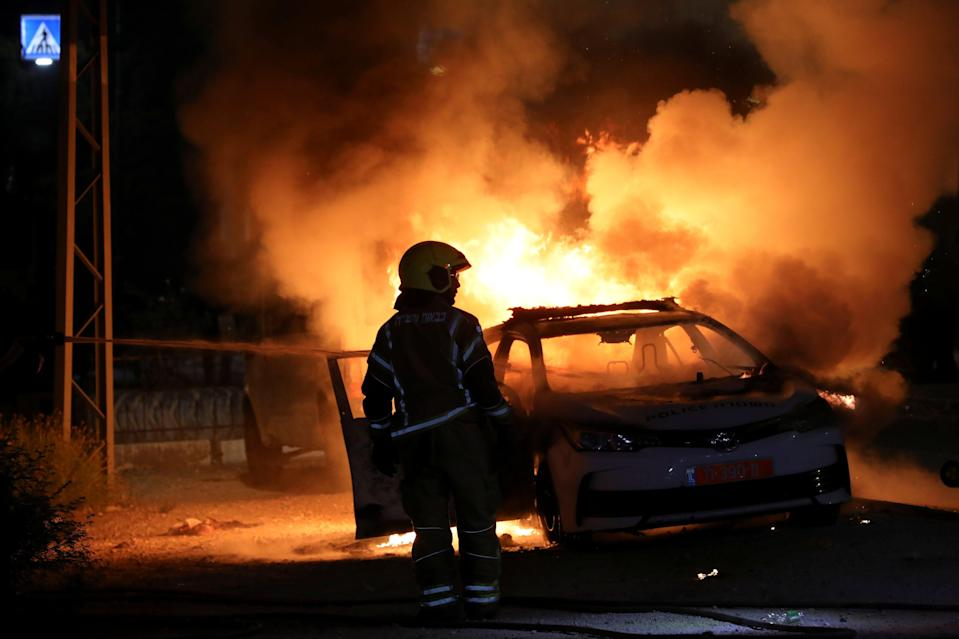<p>An Israeli firefighter by a burning police car in Lod</p> (Reuters)