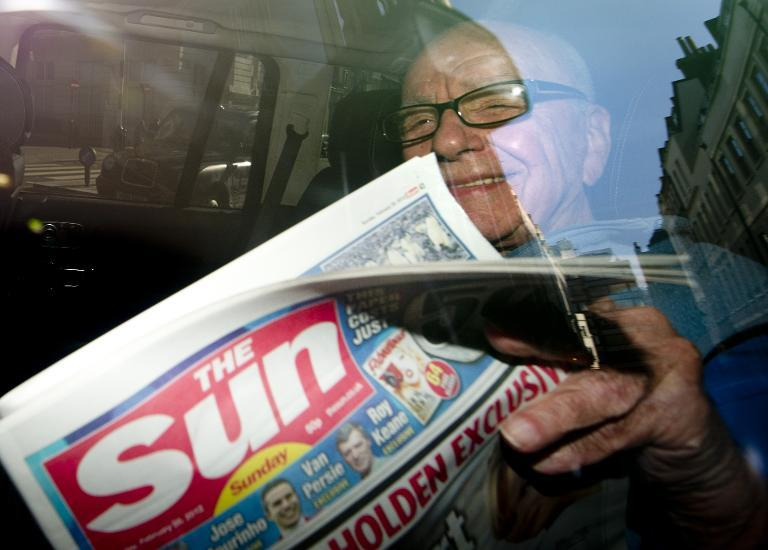 News Corporation Chief Rupert Murdoch holds up a copy of 'The Sun on Sunday' as he leaves his London home on February 26, 2012 (AFP Photo/Carl Court)