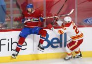 Montreal Canadiens' Brett Kulak avoids a hit from Calgary Flames' Josh Leivo during the third period of an NHL hockey game Friday, April 16, 2021, in Montreal. (Paul Chiasson/The Canadian Press via AP)