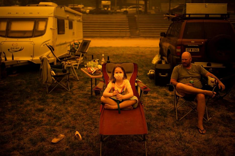 Amy and Ben Spencer sit at the show grounds in the southern New South Wales town of Bega where they are camping after being evacuated from nearby sites affected by bushfires. Source: Getty