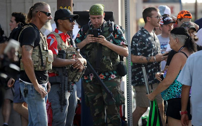Members of the boogaloo movement watch a demonstration near the BOK Center where President Trump will hold a campaign rally in Tulsa, Okla., Saturday, June 20, 2020 - Charlie Riedel/AP