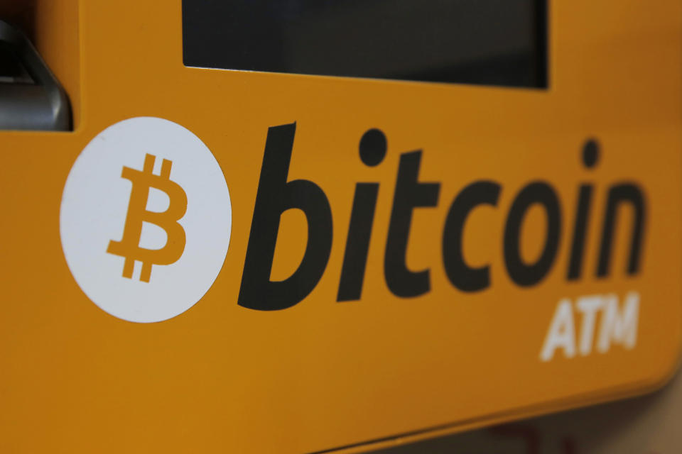 FILE - In this Dec. 21, 2017 file photo, a Bitcoin logo is shown is displayed on an ATM in Hong Kong, Thursday, Dec. 21, 2017. Tesla says it has invested more than $1 billion in Bitcoin and will accept the digital currency as payment for its electric vehicles. In a regulatory filing Monday, Feb. 8, 2021, Elon Musk's electric vehicle company said its board approved of the $1.5 billion investment and potentially more in the future. (AP Photo/Kin Cheung, File)