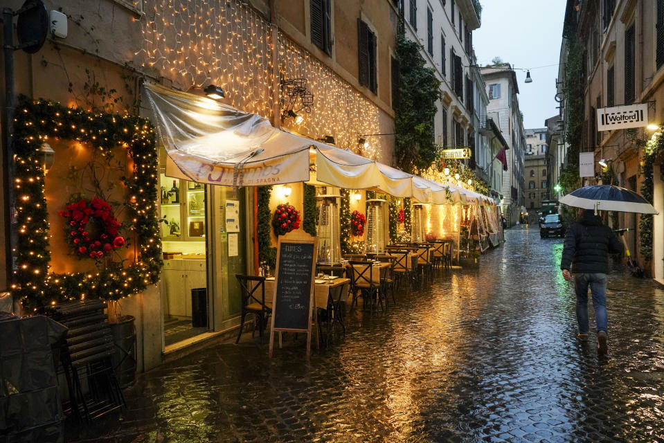 """A man walks past a restaurant with Christmas decorations, in Rome, Wednesday, Dec. 2, 2020. Italy's health minister told lawmakers on Wednesday that Italy has opted to purchase up to 202.6 million doses of anti-COVID-19 vaccines to distribute  during 2021 in """"an unprecedented effort that will require a huge collective commitment.'' (AP Photo/Andrew Medichini)"""