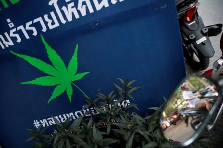 FILE PHOTO: A man drives his motorbike near an election campaign poster in Bangkok