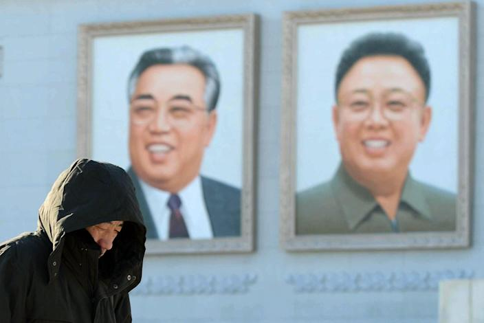 A North Korean walks near the portraits of North Korea founder Kim Il Sung, left, and late leader Kim Jong Il at Kim Il Sung Square in Pyongyang, North Korea Sunday, Dec. 9, 2012. North Korea may postpone the controversial launch of a long-range rocket that had been slated for liftoff as early as this week, state media said Sunday, as international pressure on Pyongyang to cancel the provocative move intensified. (AP Photo/Kyodo News) JAPAN OUT, MANDATORY CREDIT, NO LICENSING IN CHINA, FRANCE, HONG KONG, JAPAN AND SOUTH KOREA