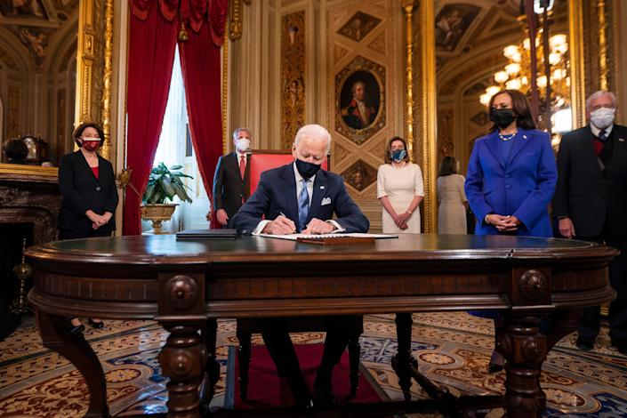 Joe Biden, watched by Kamala Harris, signs first orders as president (Getty Images)