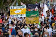 Cypriots rallied Saturday on both sides of the divided capital Nicosia, with these marchers holding placards in the self-declared Turkish Republic of Northern Cyprus