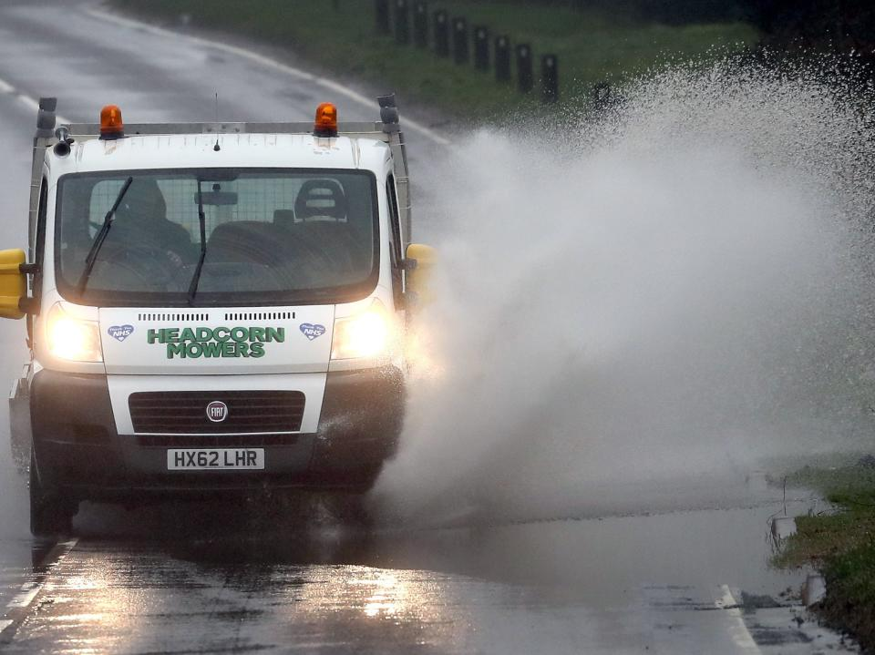 <p>A van splashes through standing water on a road near Canterbury in Kent following heavy rain</p> (PA)