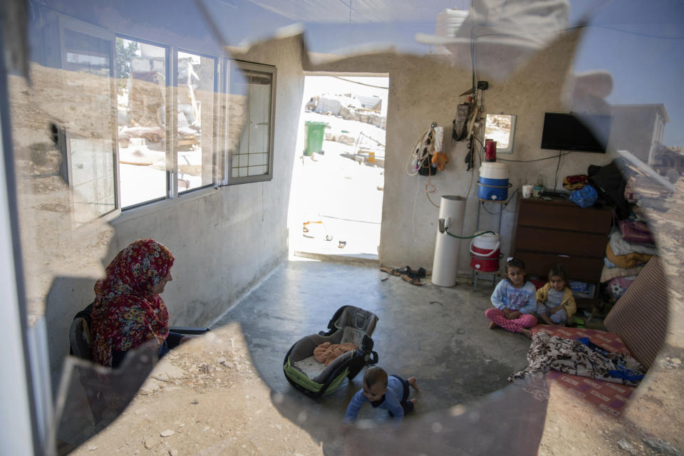 A Palestinian family is seen through their house's shattered window following a settlers' attack from nearby settlement outposts on the Bedouin community, in the West Bank village of al-Mufagara, near Hebron, Thursday, Sept. 30, 2021. An Israeli settler attack last week damaged much of the village's fragile infrastructure. (AP Photo/Nasser Nasser)