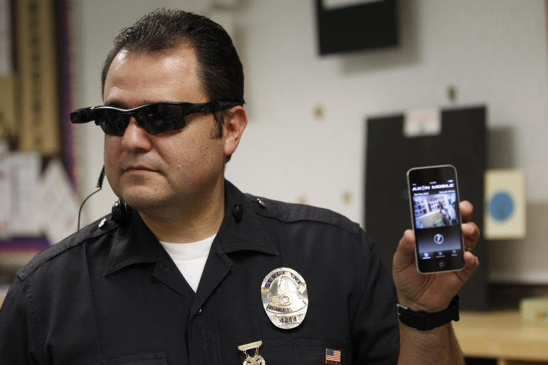 This Jan. 15, 2014 file photo shows Los Angeles Police Sgt. Daniel Gomez demonstrating a video feed from his camera into his cellphone as on-body cameras are demonstrated for the media in Los Angeles. Thousands of police agencies have equipped officers with cameras to wear with their uniforms, but they've frequently lagged in setting policies on how they're used, potentially putting privacy at risk and increasing their liability. As officers in one of every six departments across the nation now patrols with tiny lenses on their chests, lapels or sunglasses, administrators and civil liberties experts are trying to envision and address troublesome scenarios that could unfold in front of a live camera. (AP Photo/Damian Dovarganes)