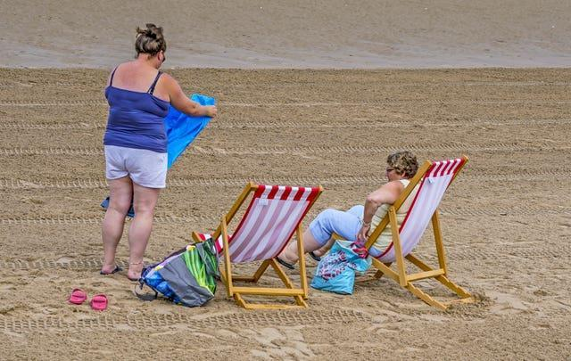 Two women use some of the new deckchairs (Peter Byrne/PA)