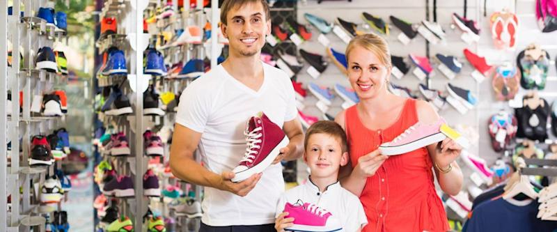 smiling spanish couple with boy choosing shoes in sport shop