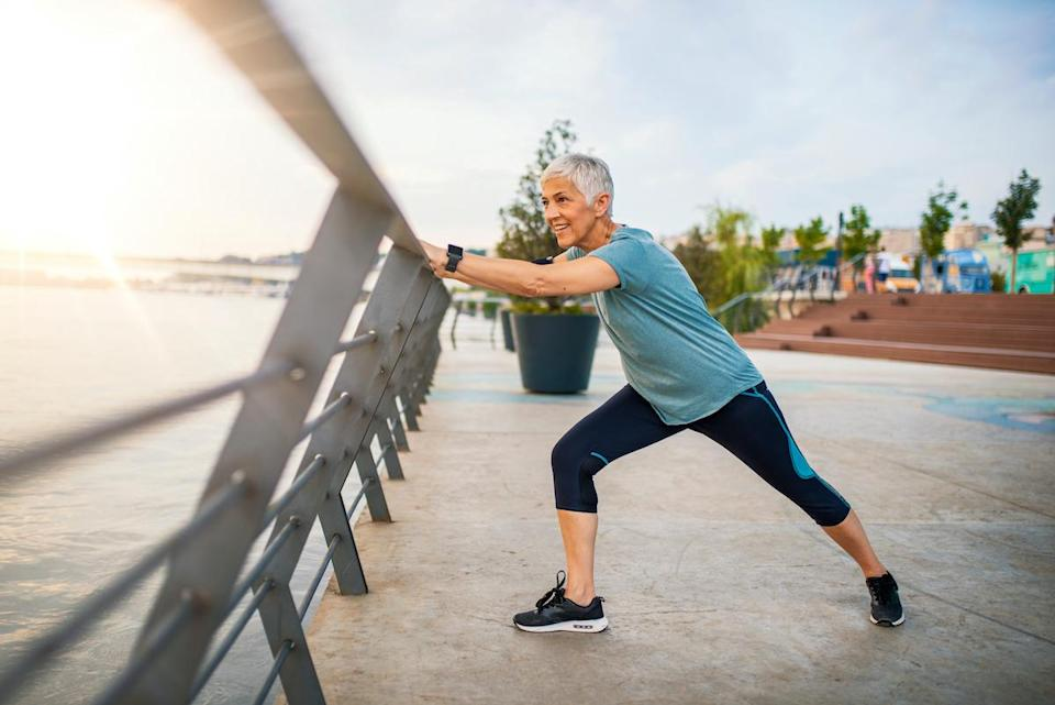 A senior woman stretches during her workout. Mature woman exercising. Portrait of fit elderly woman doing stretching exercise in park. Senior sportswoman making stretch exercises