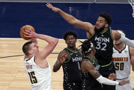 Denver Nuggets' Nikola Jokic (15) shoots as Minnesota Timberwolves' Karl-Anthony Towns (32) defends during the first half of an NBA basketball game Thursday, May 13, 2021, in Minneapolis. (AP Photo/Jim Mone)