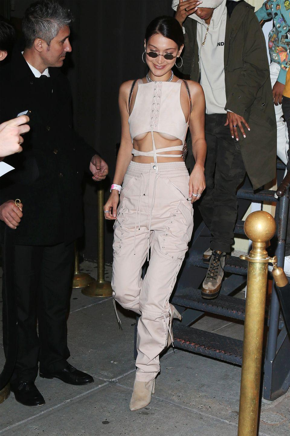<p>In high waisted nude cargo pants, a crop top, hoop earrings and nude suede boots while out shopping in New York. </p>