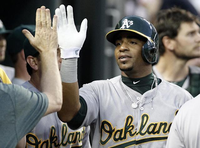 Oakland Athletics' Yoenis Cespedes gets a high-five after scoring on a single by Jed Lowrie during the sixth inning of a baseball game against the Detroit Tigers, Monday, June 30, 2014, in Detroit. (AP Photo/Duane Burleson)