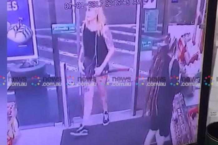 The axe-wielding woman can be seen entering the Enmore 7-Eleven in the early hours of Saturday morning. Source: News Corp