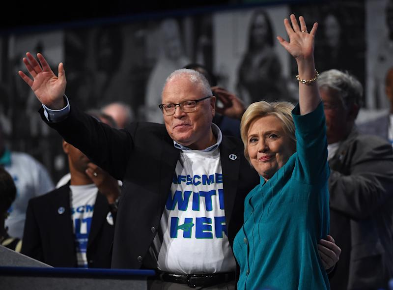 LAS VEGAS, NV - JULY 19: American Federation of State, County and Municipal Employees (AFSCME) President Lee Saunders (L) and Democratic presidential candidate Hillary Clinton wave after Clinton spoke at AFSCME's 42nd International Convention at the Las Vegas Convention Center on July 19, 2016 in Las Vegas, Nevada. Clinton continues to campaign for the general election in November while the Republicans hold their national convention. (Photo by Ethan Miller/Getty Images)