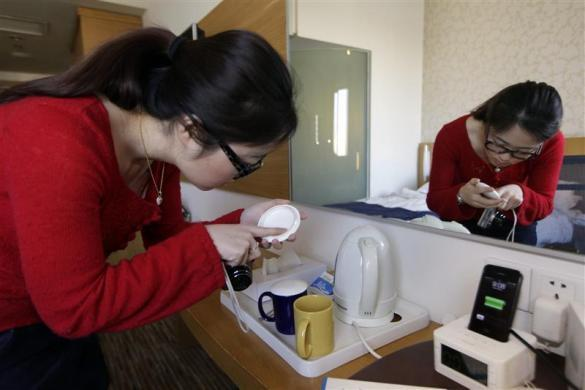 """Ms. Zhuang, a Hotel Test Sleeper, checks a tea cup at a business chain hotel, in Beijing March 6, 2012. At present, she has slept at more than 200 hotels. """"My job is to role-play travelers of different types, different ages and genders at different scenarios, and see how each hotel fits their particular needs."""" Zhuang said."""