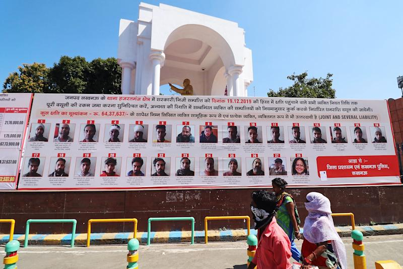 Commuters walk past a billboard installed by Uttar Pradesh authorities displaying pictures, names and addresses of people accused of vandalism. (Photo by STR / AFP) (Photo by STR/AFP via Getty Images)