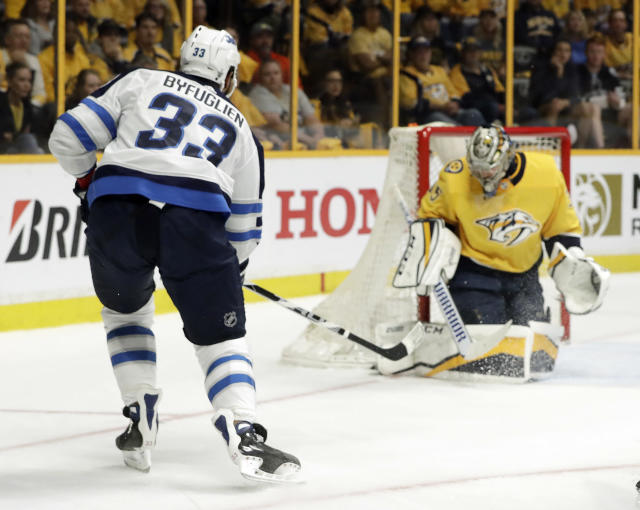 Winnipeg Jets defenseman Dustin Byfuglien (33) scores a goal against Nashville Predators goalie Pekka Rinne, right, of Finland, during the first period in Game 2 of an NHL hockey second-round playoff series Sunday, April 29, 2018, in Nashville, Tenn. (AP Photo/Mark Humphrey)