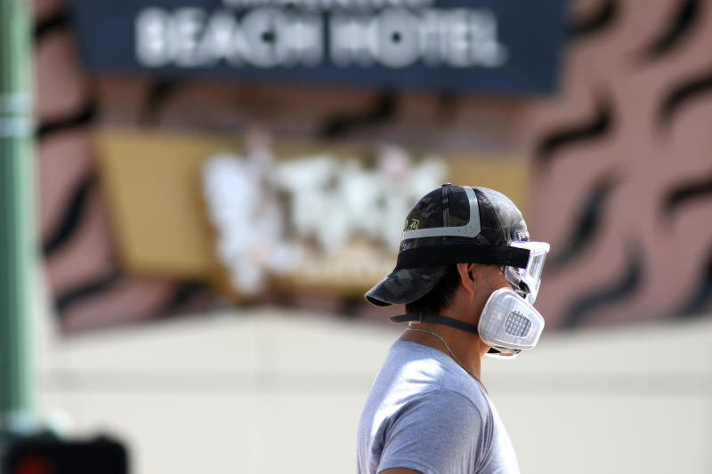 A man wears goggles and a mask as he walks a dog along Waikiki Beach in Honolulu on Saturday, March 28, 2020. Like many cities across the world, Honolulu came to an eerie standstill this weekend as the coronavirus pandemic spread throughout the islands. But Hawaii officials went beyond the standard stay-at-home orders and effectively flipped the switch on the state's tourism-fueled economic engine in a bid to slow the spread of the virus. As of Thursday, anyone arriving in Hawaii must undergo a mandatory 14-day self-quarantine. The unprecedented move dramatically reduced the number of people on beaches, in city parks and on country roads where many people rely on tourism to pay for the high cost of living in Hawaii. (AP Photo/Caleb Jones)