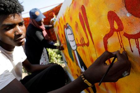 FILE PHOTO: Artists work on a graffiti on a wall near the defence ministry compound in Khartoum, Sudan, April 24, 2019. REUTERS/Umit Bektas/File Photo