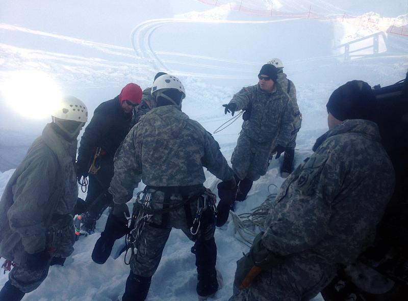 In this photo provided by the U.S. Army and taken Sunday April 14, 2013, members of the Army's Alaska Northern Warfare Training Center prepare to descend 145 feet to a 15-foot space inside an Alaska glacier in the Hoodoo Mountains to extract the body of a 9-year-old boy who fell through the hole on his snowmobile on Saturday. The men on Sunday shoveled 3,000 pounds of snow into bags lifted out by soldiers at the surface to reach the body of Shjon Brown. (AP Photo/U.S. Army)