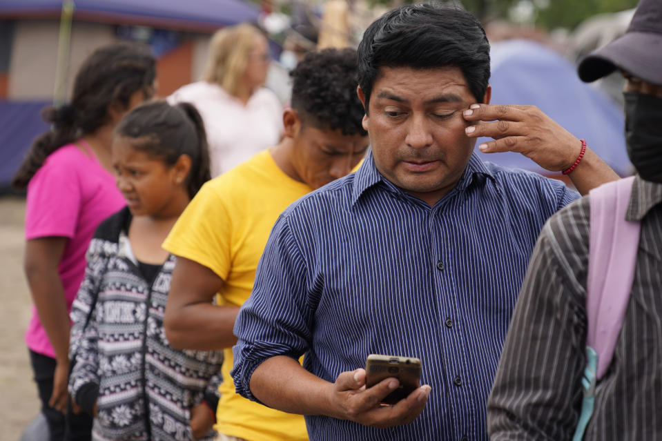 Jose Rodriguez, of Honduras, wipes his eye as he waits in line for food donated by a local church at a makeshift camp for migrants near the U.S.-Mexico border Thursday, May 13, 2021, in Reynosa, Mexico. Growing numbers of migrant families are making the heart-wrenching decision to separate from their children and send them into the U.S. alone. . (AP Photo/Gregory Bull)