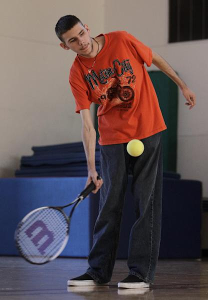 In this photo taken Oct. 16, 2012, Austin Benavidez, who is blind, returns a volley using an oversized ball filled with ball bearings at the California School for the Blind in Fremont, Calif. Students at the school are learning to play tennis, and expanding the boundaries of what the blind can do while offering new insights into the human mind. They must turn their ears into eyes, listening for the ball's bounce to figure out where to swing their rackets. (AP Photo/Ben Margot)