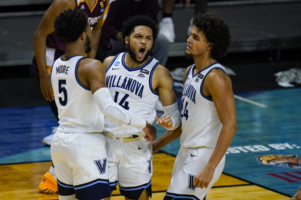 Villanova guard Caleb Daniels (14) celebrates a defensive stop with Justin Moore (5) and Jeremiah Robinson-Earl (24) in the second half of a first round game against Winthrop in the NCAA men's college basketball tournament at Farmers Coliseum in Indianapolis, Friday, March 19, 2021. (AP Photo/Michael Conroy)