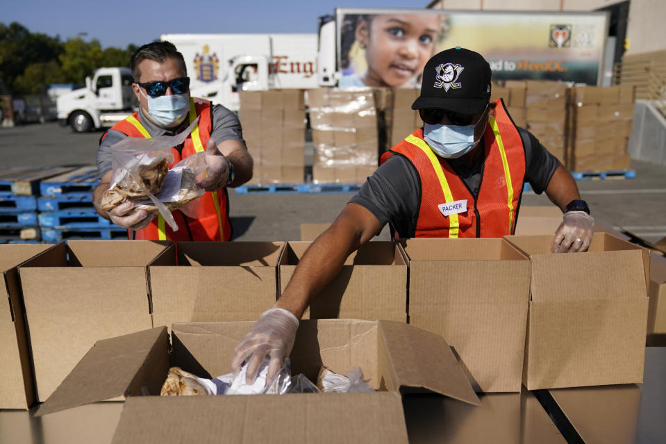 Chris Kenyon, left, and Gavin Maske pack boxes of food outside Second Harvest Food Bank Thursday, Nov. 19, 2020, in Irvine, Calif. The boxes will be distributed to families in need on Thanksgiving Day at the Honda Center in Anaheim, Calif. As COVID spreads and unemployment rates rise, food distribution centers see an increase in need for the holidays. (AP Photo/Ashley Landis)