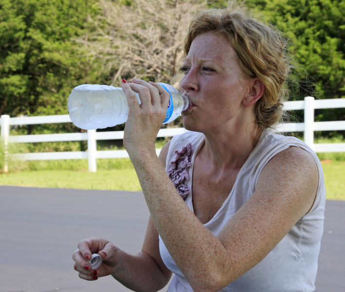 Landscaper Heather Parrott, owner of Neighborhood Gardner, takes a break to drink some water while working on the landscaping at a housing development in Edmond, Okla., Tuesday, June 26, 2012. in Edmond, Okla., Tuesday, June 26, 2012. Parrott said that this year's heat is not as bad as last years's, because it came on gradually, allowing her body to acclimate to it. (AP Photo/Sue Ogrocki)