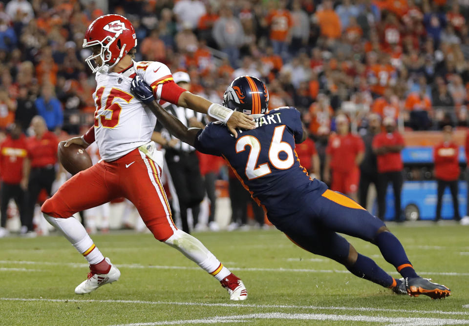 Kansas City Chiefs quarterback Patrick Mahomes (15) escapes the tackle of Denver Broncos defensive back Darian Stewart (26) during the second half of an NFL football game, Monday, Oct. 1, 2018, in Denver. (AP Photo/Jack Dempsey)