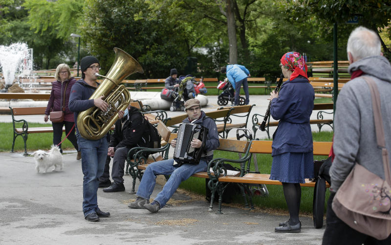 Musicians play music in a park in Vienna, Austria, Friday, May 1, 2020, after the Austrian government eased the movement of people. The Austrian government has moved to restrict freedom of movement for people, in an effort to slow the onset of the COVID-19 coronavirus. (AP Photo/Ronald Zak)