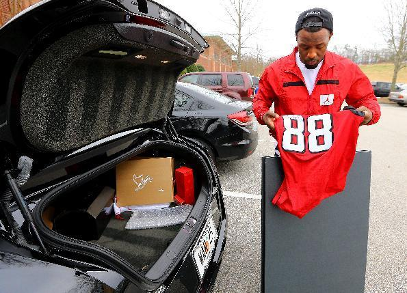Atlanta Falcons safety William Moore packs his trunk after cleaning out his equipment locker, including an autographed Tony Gonzalez jersey, after the team's NFL football player exit interviews to close out the season on Monday, Dec. 30, 2013, in Flowery Branch, Ga. (AP Photo/Atlanta Journal-Constitution, Curtis Compton)