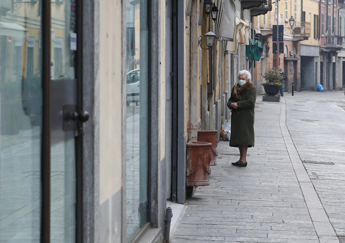 In this photo taken on Thursday, March 12, 2020, an elderly woman wearing a mask waits to enter a deli meat and cold cuts shop in Codogno, Italy. The northern Italian town that recorded Italy's first coronavirus infection has offered a virtuous example to fellow Italians, now facing an unprecedented nationwide lockdown, that by staying home, trends can reverse. Infections of the new virus have not stopped in Codogno, which still has registered the most of any of the 10 Lombardy towns Italy's original red zone, but they have slowed. For most people, the new coronavirus causes only mild or moderate symptoms. For some it can cause more severe illness. (AP Photo/Antonio Calanni)