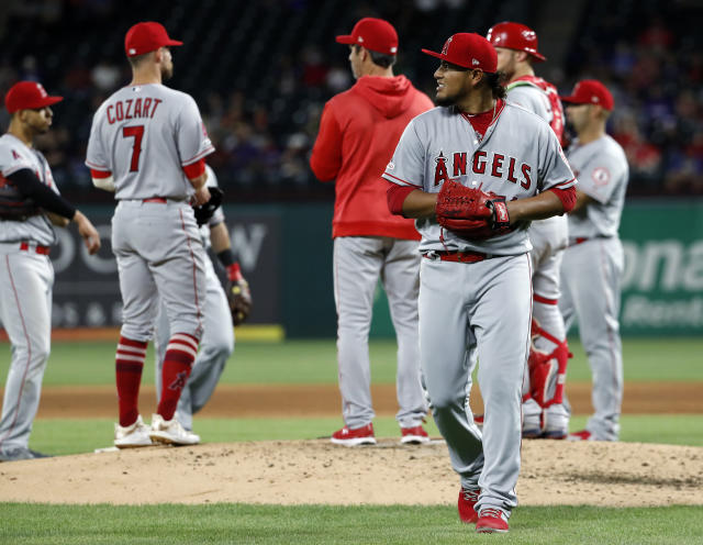 Los Angeles Angels starting pitcher Jaime Barria walks to the dugout after turning the ball over to manager Brad Ausmus, center rear, during the sixth inning of a baseball game against the Texas Rangers in Arlington, Texas, Tuesday, April 16, 2019. (AP Photo/Tony Gutierrez)