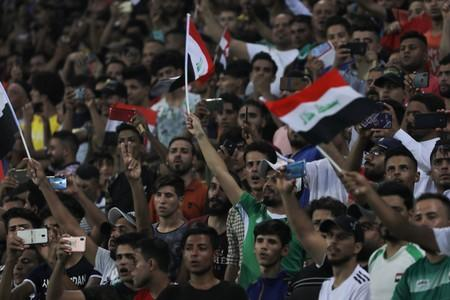 Iraqi soccer fans cheer on their team during the game of the West Asia Football Federation Championship between Iraq and Lebanon in the holy city of Kerbala