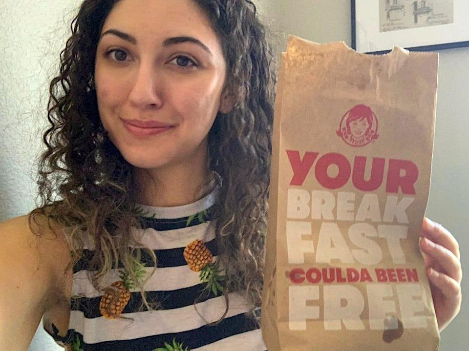 The writer holding a bag of Wendy's breakfast
