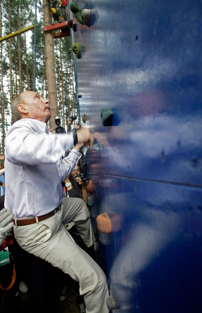 Russian Prime Minister Vladimir Putin scales a climbing wall during his visit at a summer camp run by the Nashi youth group at Lake Seliger in the central Tver region on Aug. 1, 2011.