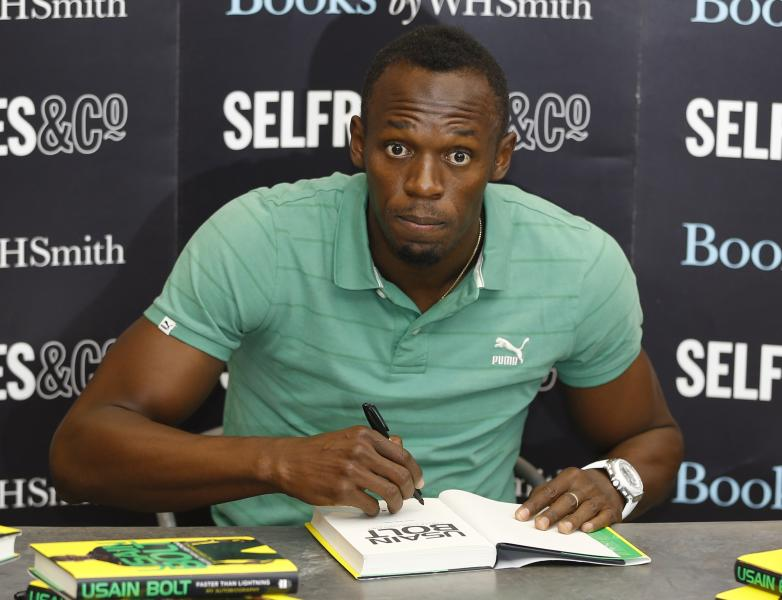 Jamaican athlete Usain Bolt, poses for the media as he signs a copy of his new autobiography called 'Faster than Lightning' at a department store in London, Thursday, Sept. 19, 2013. (AP Photo/Kirsty Wigglesworth)